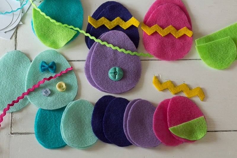 Egg shapes cut from colorful felt with buttons and ricrac