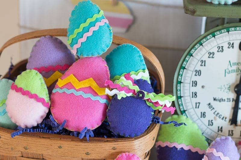 Colorful Felt Easter Eggs on Display in basket with purple paper straw, vintage scale and cut out bunny background