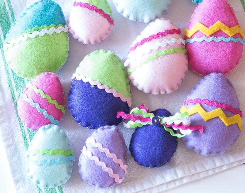 Finished colorful felt Easter Eggs laid out on pretty flour sack towel