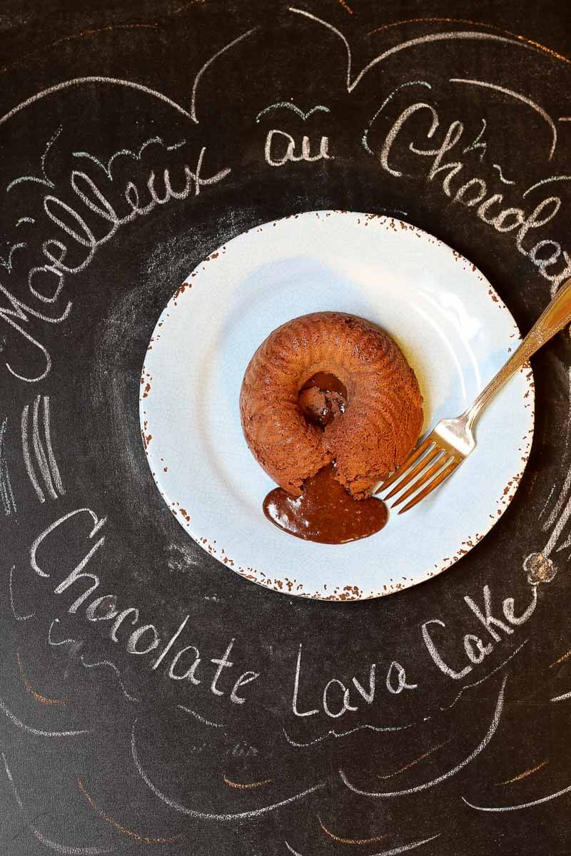 Chocolate Lava Cake on Blue plate with antique fork on a chalkboard background