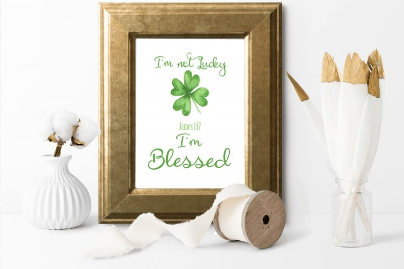 I'm not lucky, I'm blessed printable with four-leaf clover in gold frame with cotton stems and gold-tipped white feathers