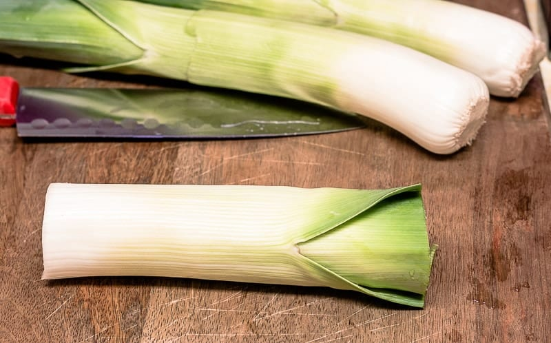 Leeks on cutting board with roots and tops cut off.