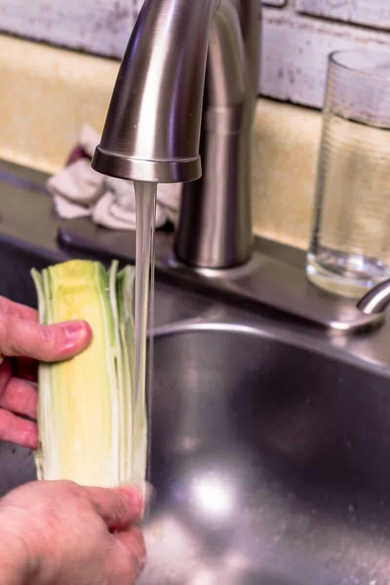 Leeks being rinsed under faucet.