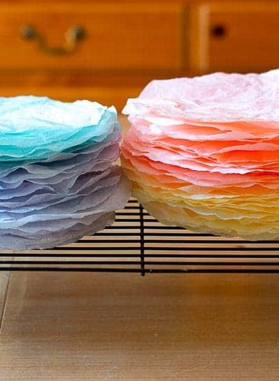 Brightly colored coffee filters dyed with food coloring on drying rack