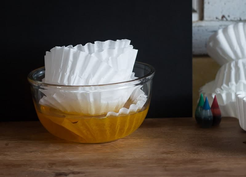 Coffee filters being placed in glass bowl filled with yellow food coloring diluted with water
