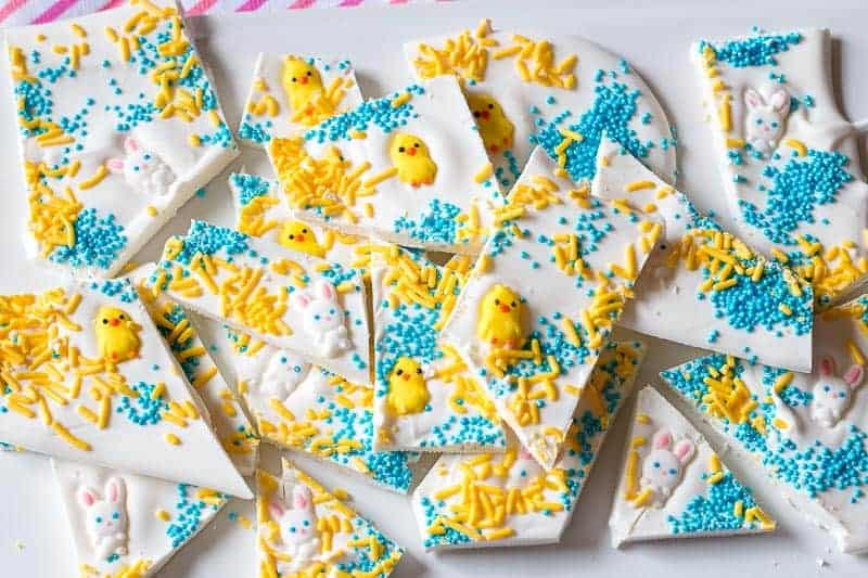 Easter candy bark cut into pieces on white platter