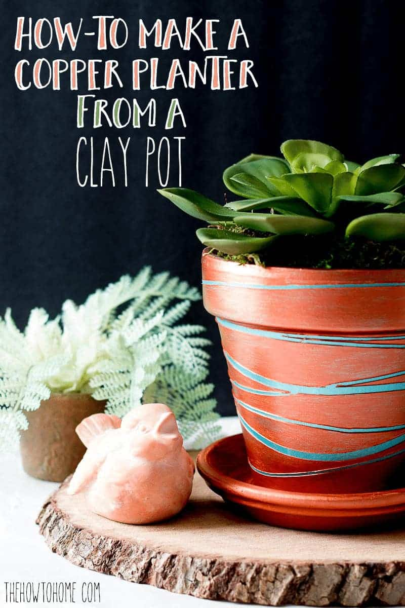 Metallic copper terracotta pot with a faux succulent on top of a wood slice in front of a black background
