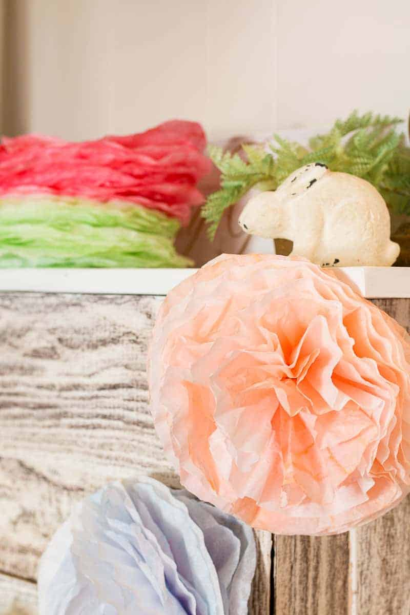 Close up of coffee filter pom pom garland flower hanging on faux fireplace mantle