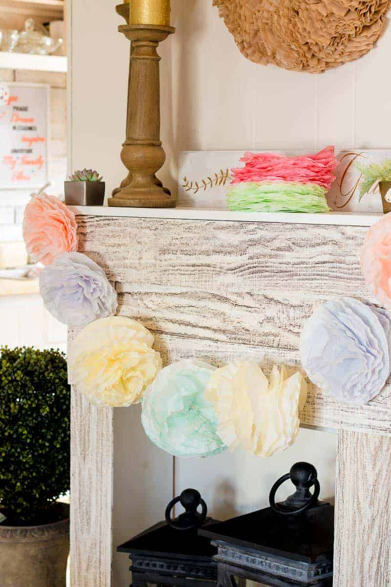 Coffee filter pom pom garland hanging on faux fireplace