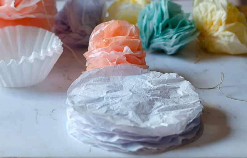 stack of colored coffee filters as part of tutorial for how to make coffee filter pom pom garland