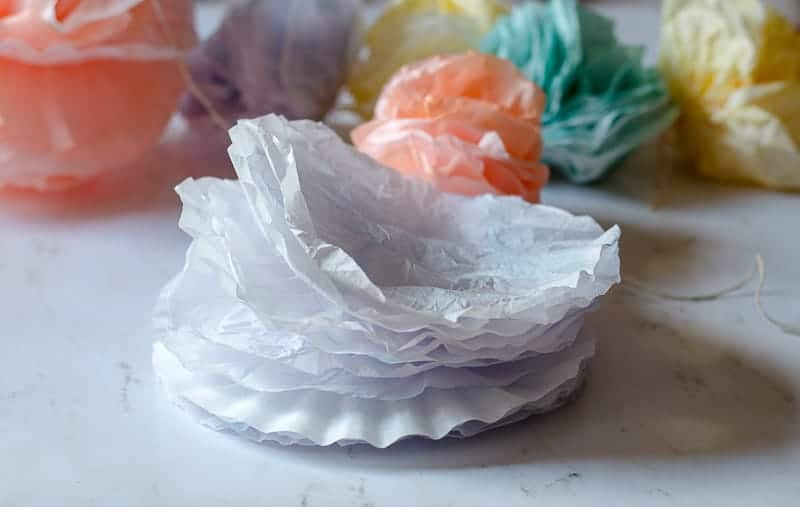 Stack of dyed coffee filters ready to be made into a coffee filter pom pom garland