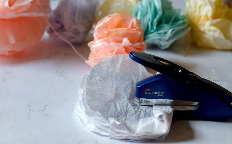 Coffee filter pom pom garland flower making process with filters folded in half and being stapled