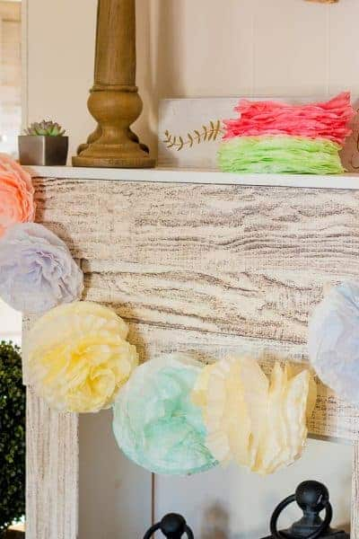 Coffee filter pom pom garland hanging from faux fireplace in bright colors