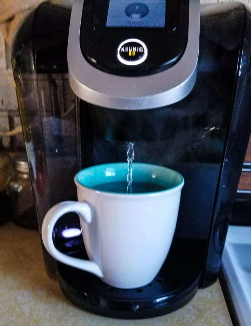Photo of Keurig 2.0 dispensing Keurig Descaling Solution into white coffee cup with blue interrior