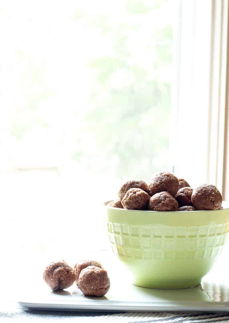 Green bowl filled with homemade no bake chocolate chip cookie dough protein bites