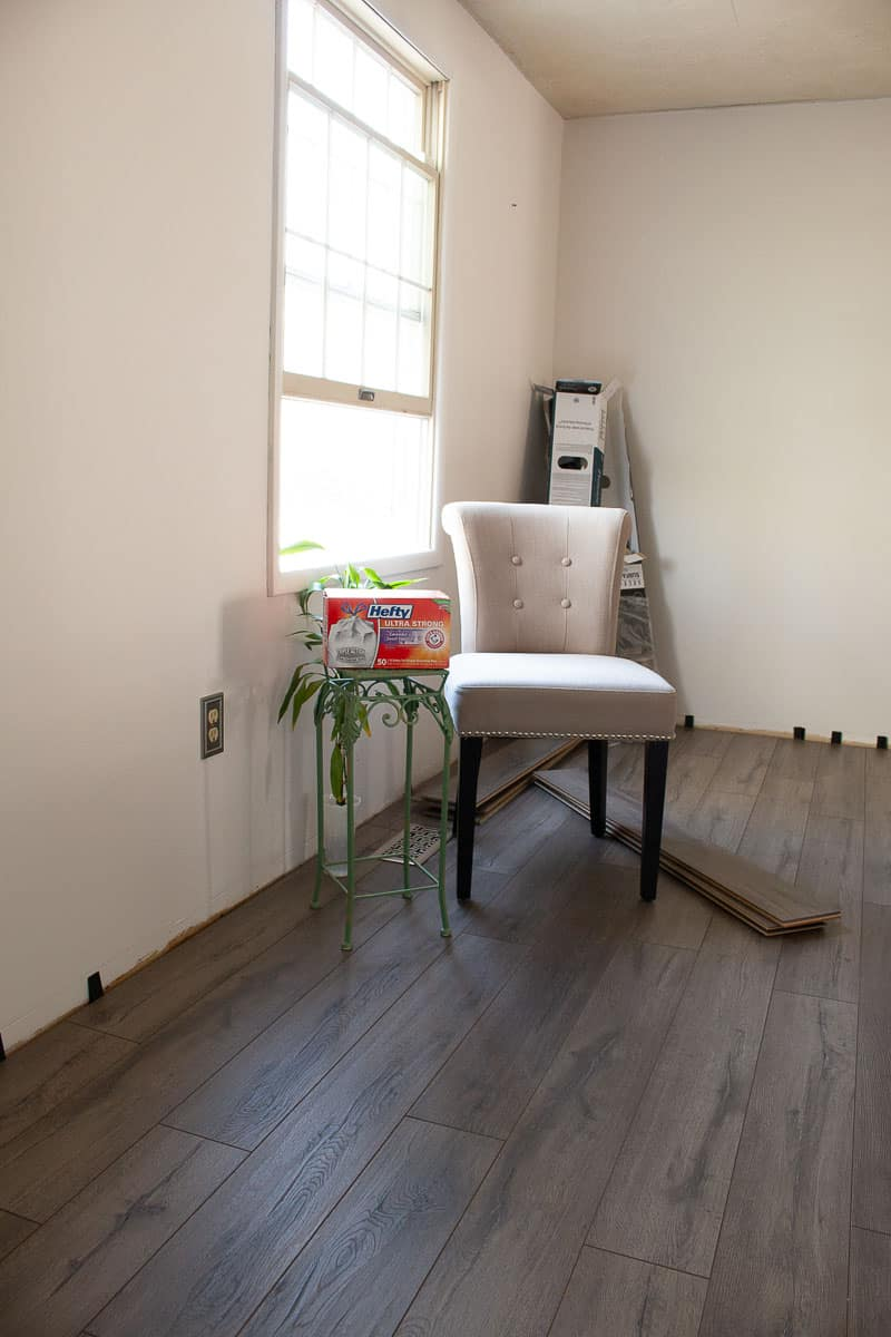 New dining room floors with formal chair, farmhouse flooring planks on floor, green plant stand and box of Hefty Trash Bags