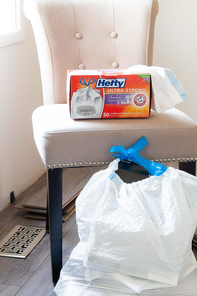 Hefty trash bag box on formal dining room chair with filled Hefty Trash Bag in front of chair on farmhouse plank flooring during kitchen remodel