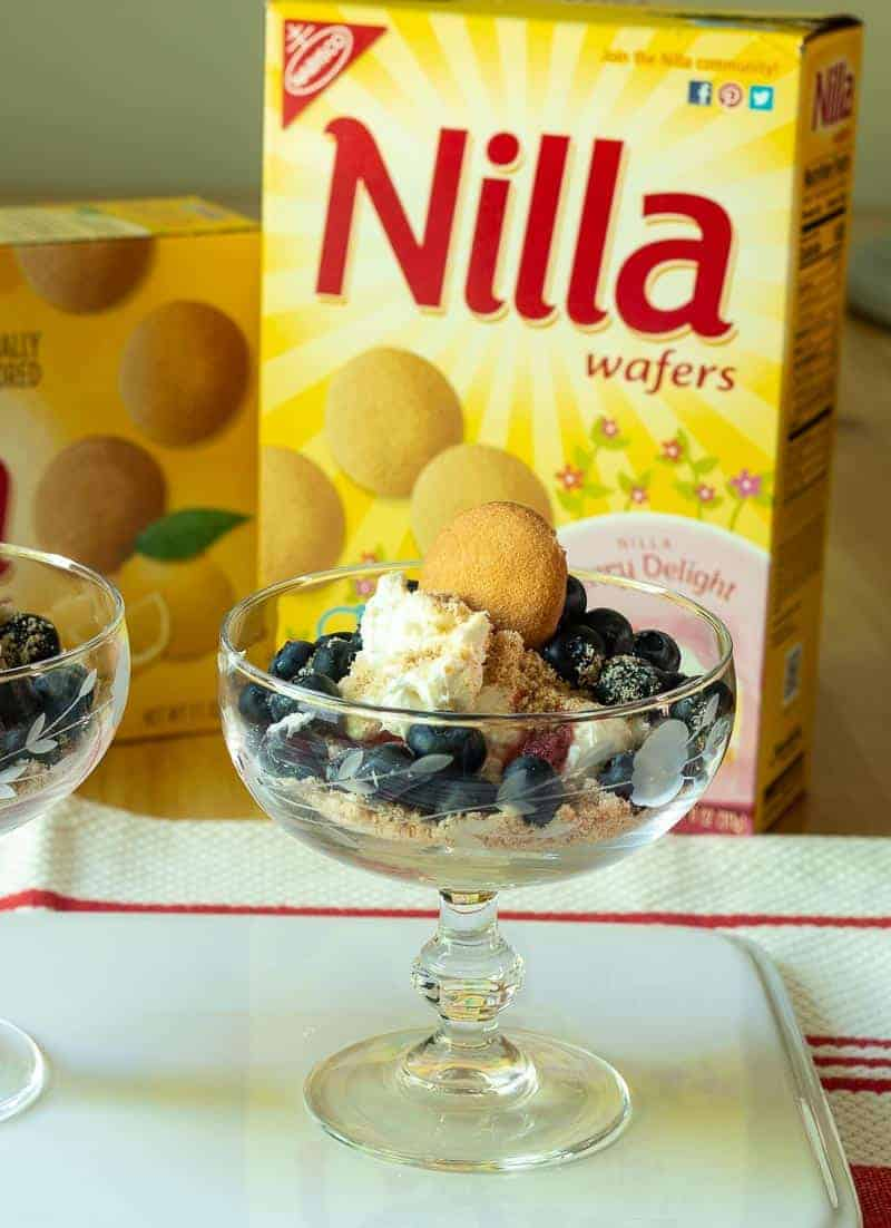 Front view of No Bake NILLA Wafer Cheesecakes with Fresh Berries and a NILLA Wafer Garnish in front of a box of NILLA Wafers