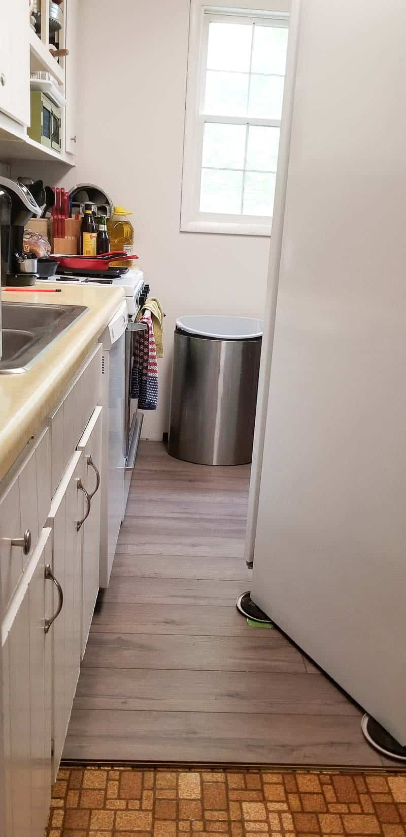 Refrigerator pulled away from wall and placed on new farmhouse plank flooring