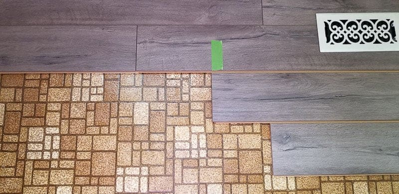 Side by side before and after - 1970's brown linoleum flooring next to Farmhouse Plank Flooring - floating click and lock type