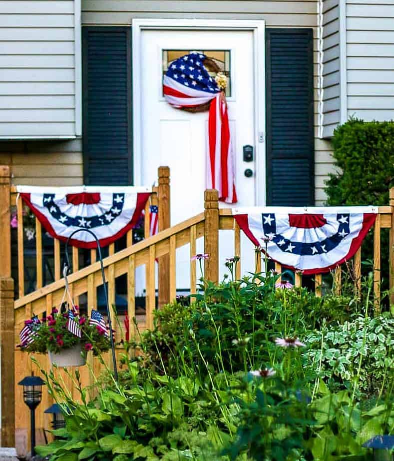 White front door with American Flag Wreath and two red, white, and blue buntings on a porch.