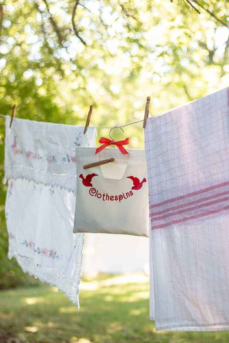 Laundry and clothespin bag hanging on clothesline outside