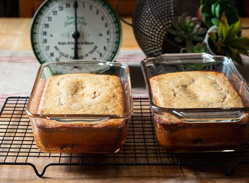 Loaf of protein banana bread in clear glass bread baking pan on black wire rack with vintage green scale in background