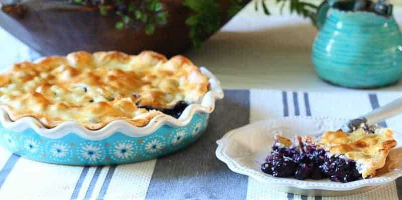Fresh homemade blueberry pie with slice of blueberry pie on plate