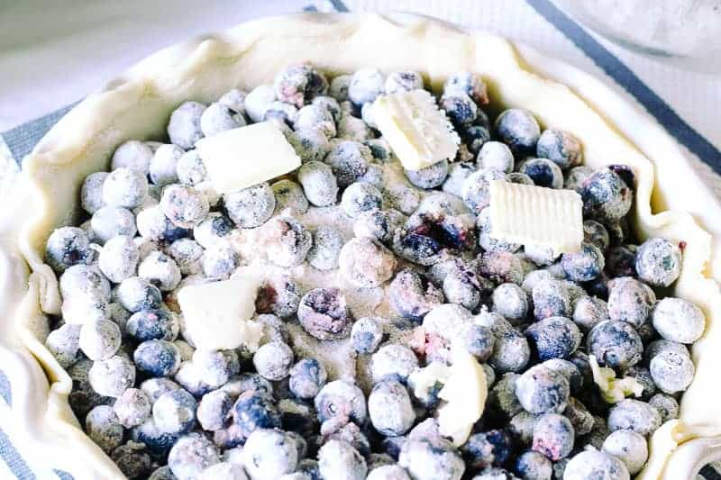 fresh blueberry pie filling dotted with cold butter in pie crust in pie dish