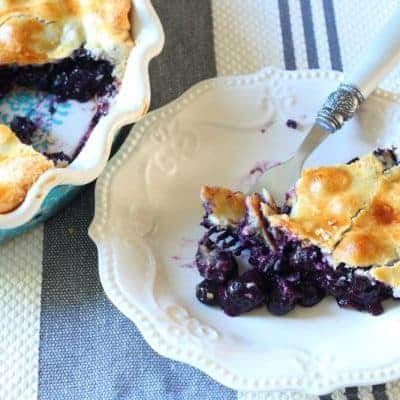 Slice of fresh blueberry pie on white plate with Pioneer Woman silverware fork