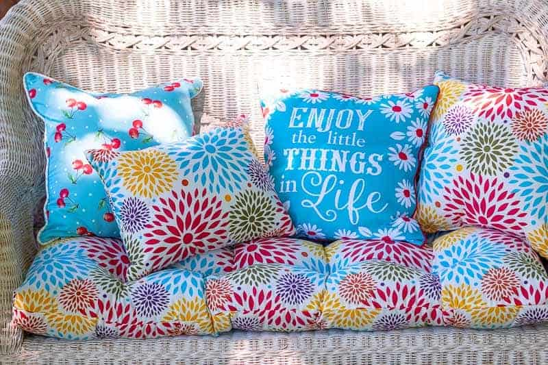 White wicker sofa with brightly colored cushions and pillows