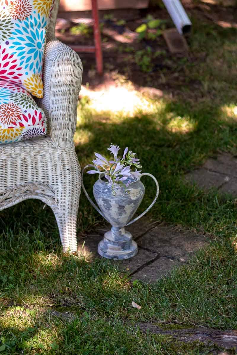 Small faux vintage trophy filled with hosta blooms in yard