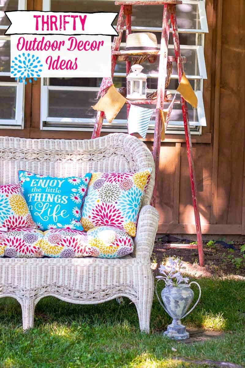 White wicker settee with cushions, vintage ladder, and trophy filled with flowers