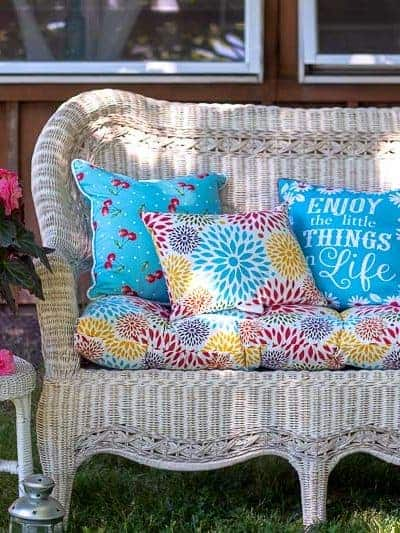 White wicker sofa with colorful cushions and pillows