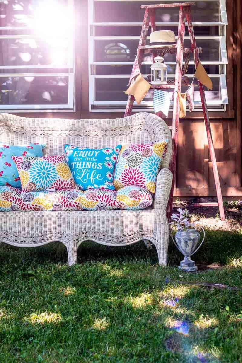 White wicker sofa, faux trophy filled iwth hosta blooms, and red wooden ladder in yard