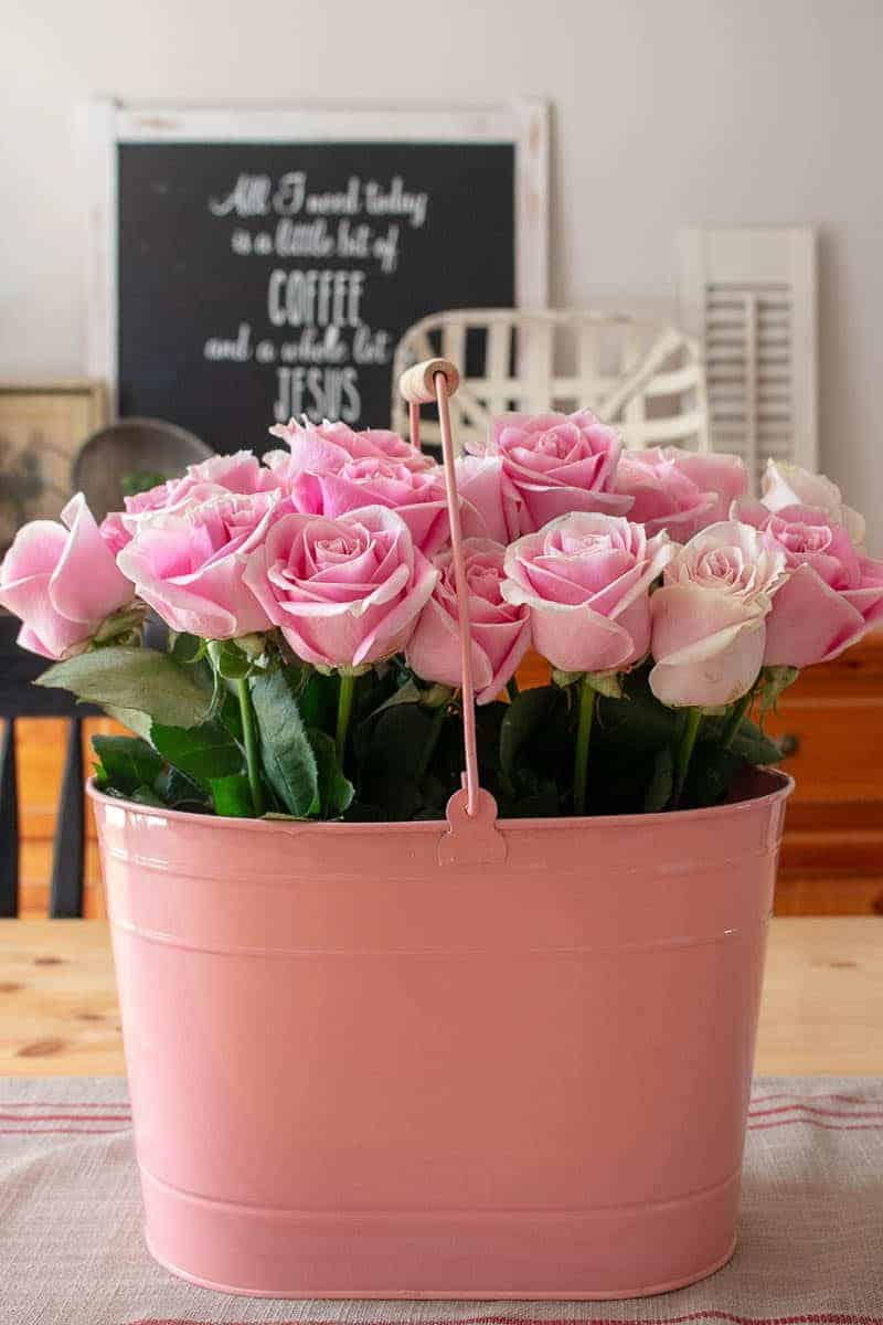 How to arrange flowers - Two dozen pink roses in a pink oblong metal pail on dining room table