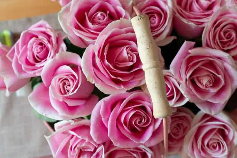 How to arrange flowers - Overhead view of bouquet of pink roses in a large pink pail