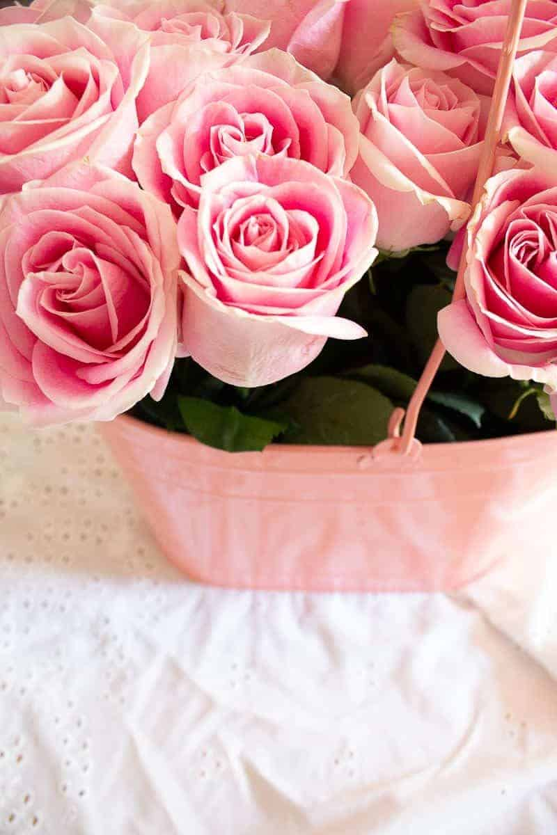How to arrange flowers - Overhead view of beautiful pink roses in a pink bucket on top of white eyelet fabric