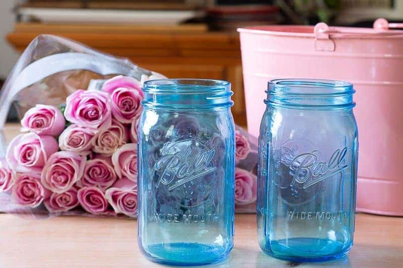 How to arrange flowers - Two blue tinted mason jars on table in front of two dozen pink roses and a large pink metal bucket