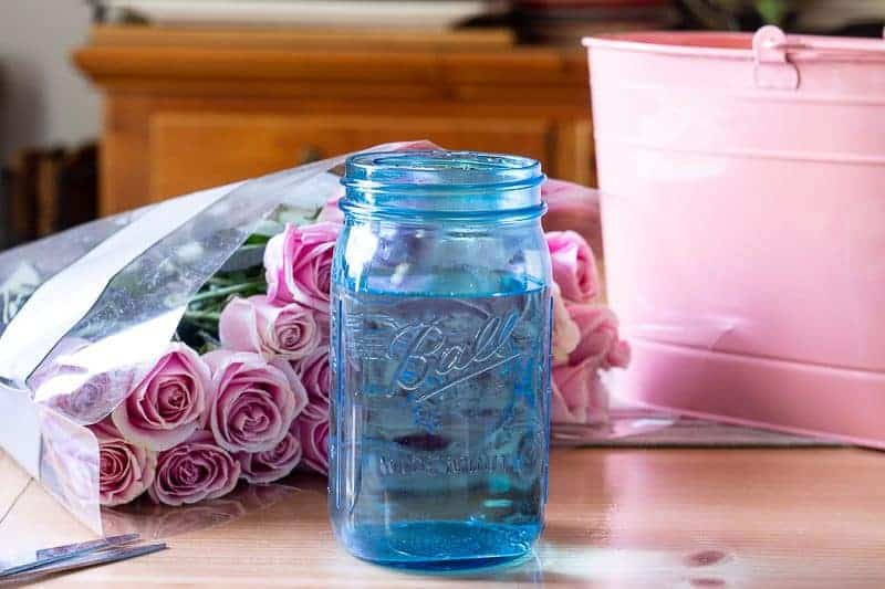 How to arrange flowers - Pink metal oblong pail, two dozen pink roses and a blue Ball mason jar on dining room table