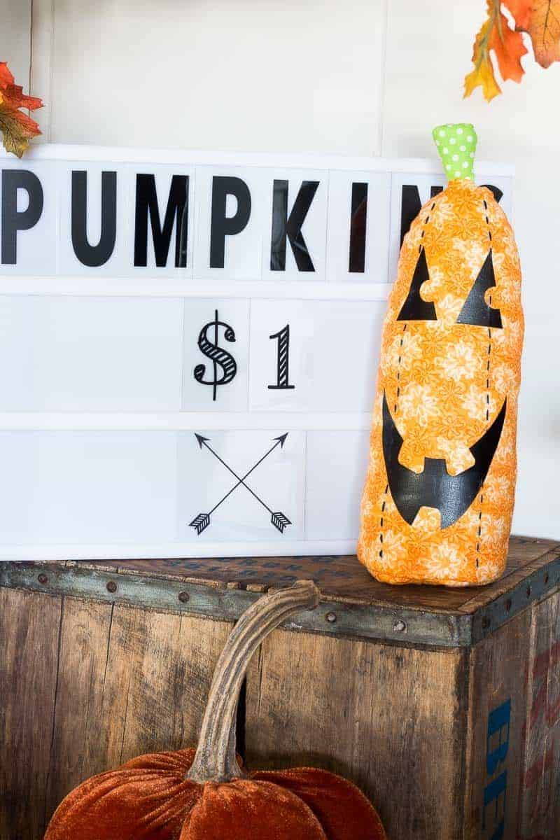 Fabric stuffed pumpkin on a wooden crate in front of a lightbox that says Pumpkins $1