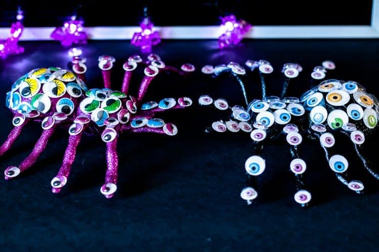 side view of dollar store Halloween craft of two plastic spiders covered in googly eyes