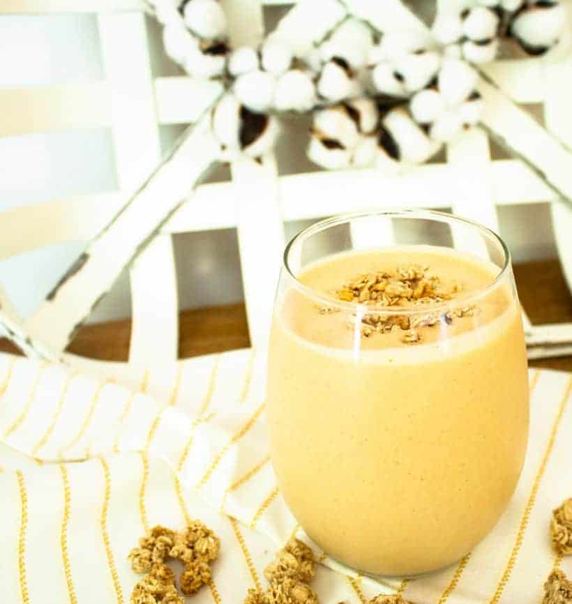 Healthy pumpkin pie smoothie in glass with granola