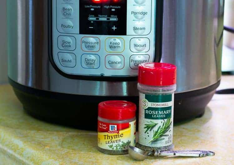 Instant pot on countertop with dried thyme and rosemary and measuring spoon