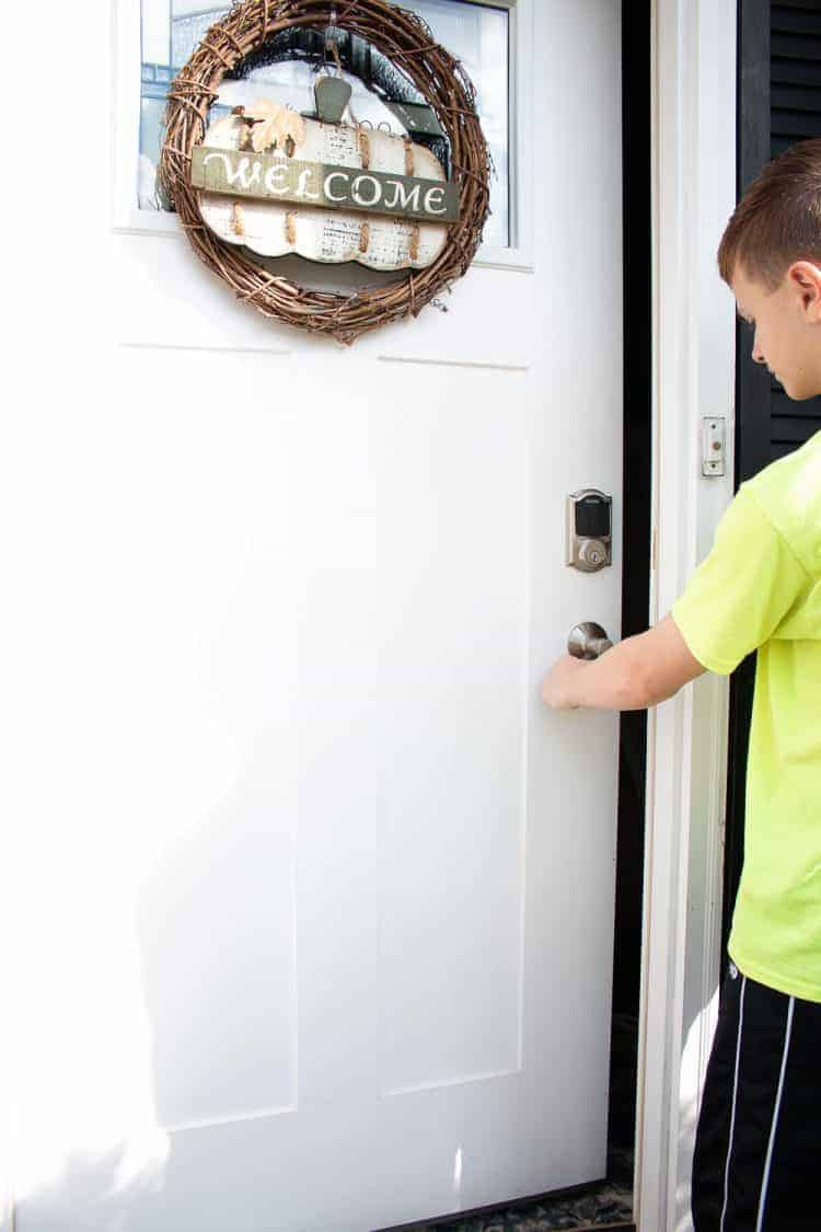 Boy in yellow shirt opening white front door using Schlage Connect Smart Lock