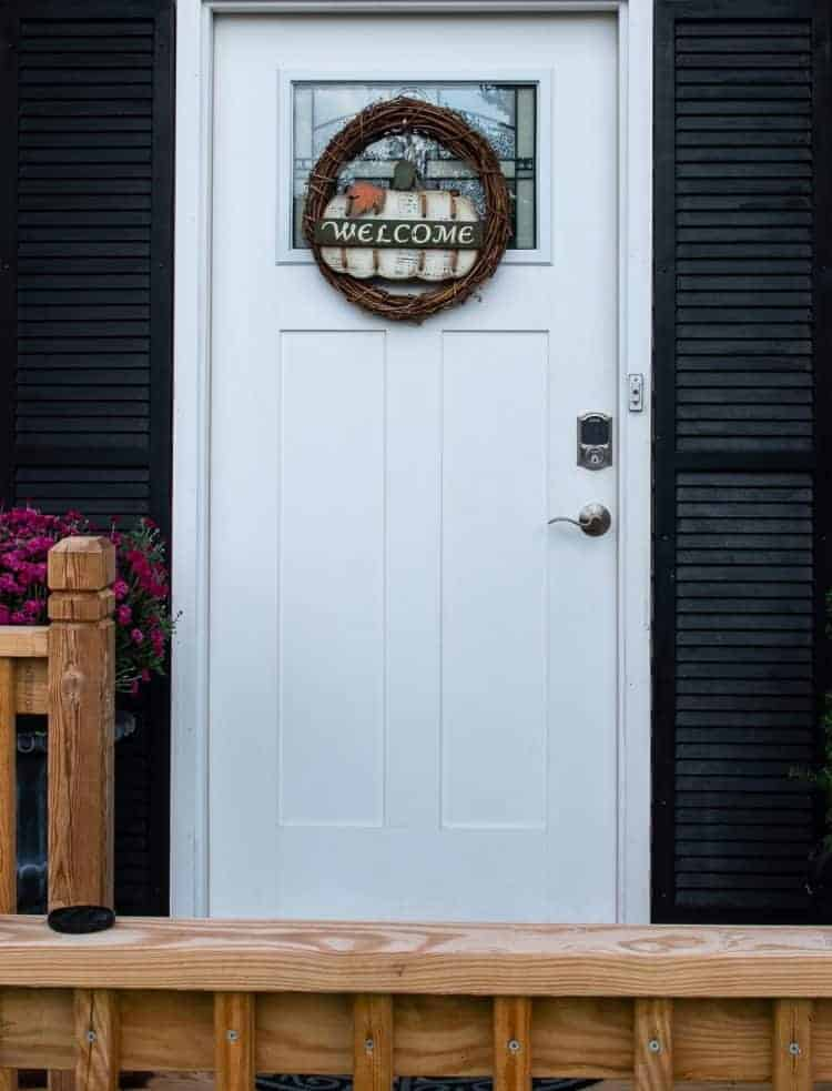 White front door flanked with black shutters and new Schlage Connect Smart Lock installed
