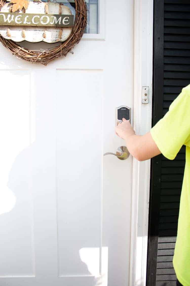 Boy opening Schlage Connect smart lock on front door