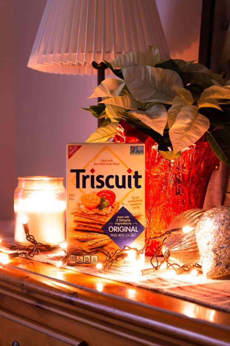 Box of Triscuit crackers on buffet with white Christmas lights, a candle, and a white poinsettia