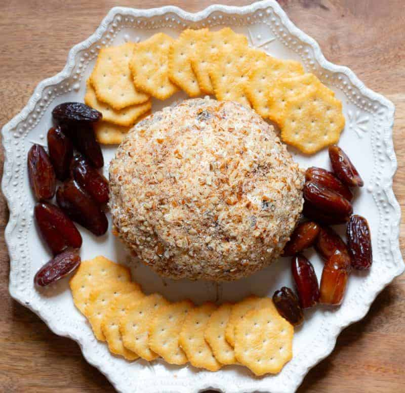 Overhead view of a pineapple cheese ball rolled in pecans on a white platter with butter crackers and dates around it