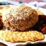 Pineapple Cheese Ball rolled in pecans on a beautiful white platter with dates and butter crackers
